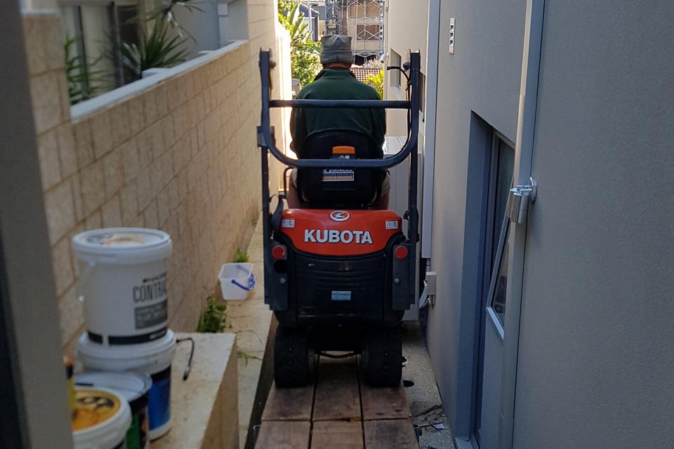 Mini excavator gaining access down ramp