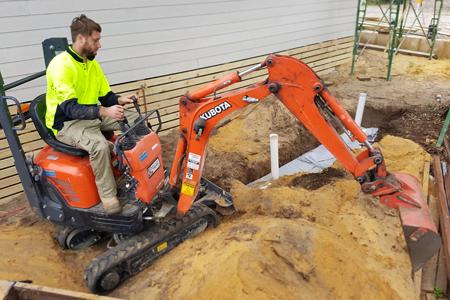 Mini excavator with operator