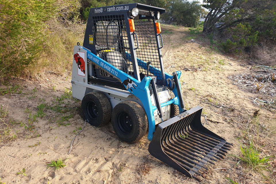 Skid steer fitted with rake bucket